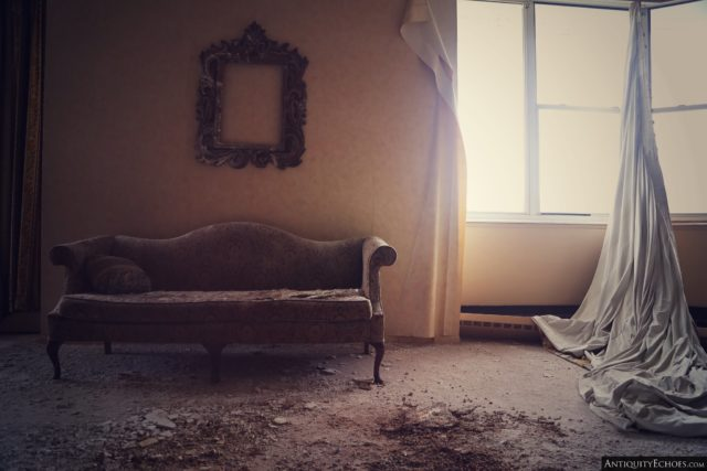 Old-style couch and empty picture frame placed to the left of a sunlit window