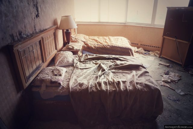 Two unmade beds separated by a bedside table and lamp