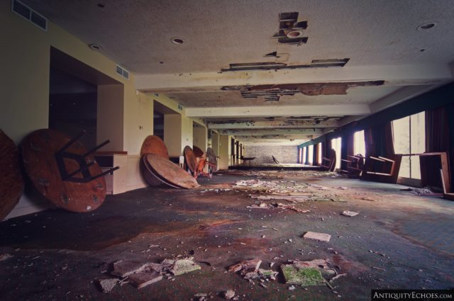 A large room with debris on the ground and round wooden tables up against the wall