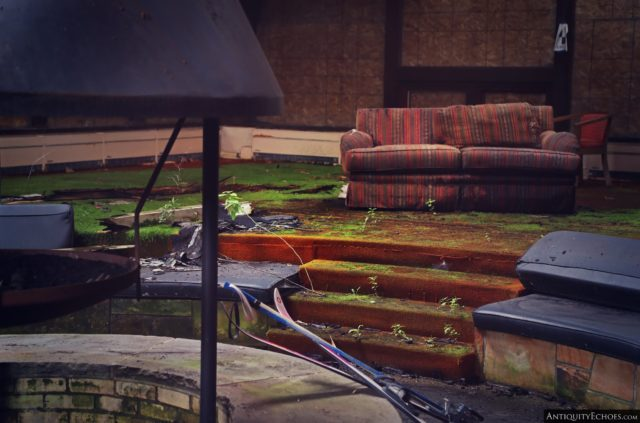 A red couch placed near some low-lying steps near an indoor fire pit