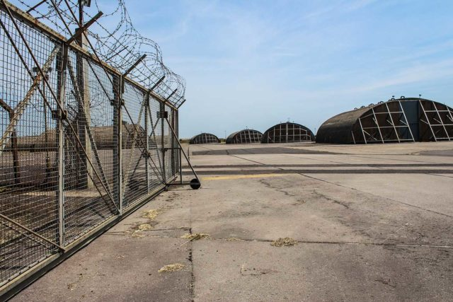 Concrete ground with a barbed wire fence to the left and an airplane hanger to the right