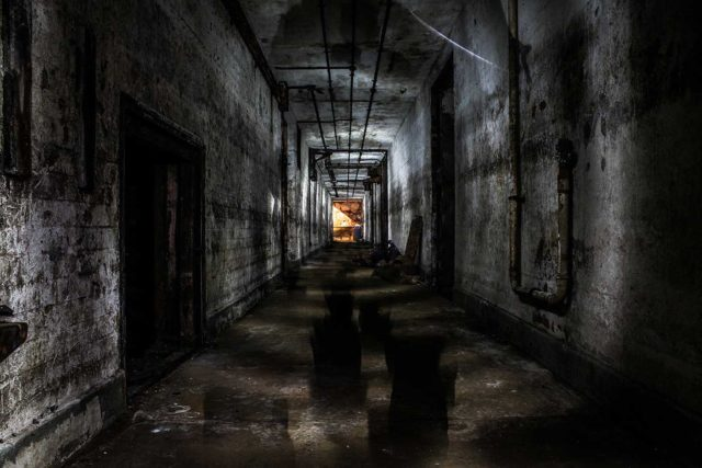 A dark hallway with a lit doorway at the end.