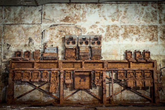 Rusty radar equipment placed against a concrete wall
