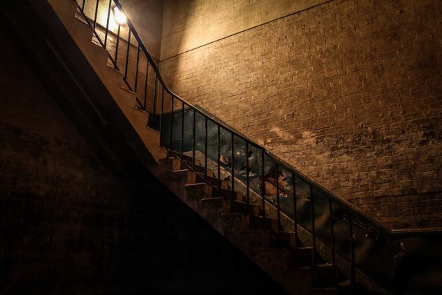 View of a darkened staircase from below.