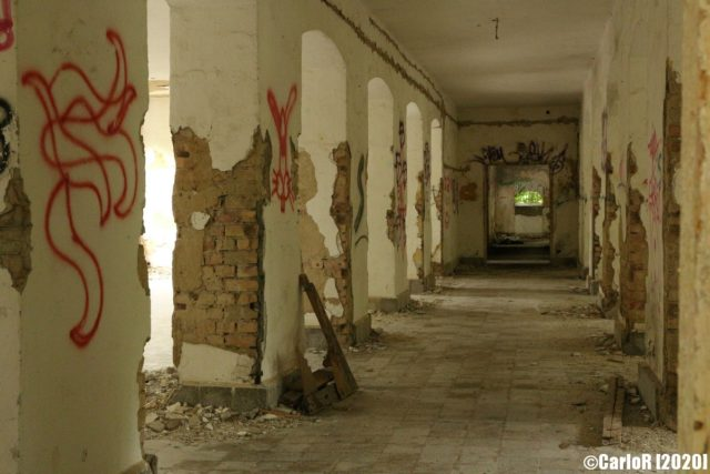 Outdoor corridor with graffiti on the walls