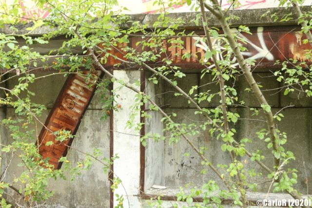 Rusty sign attached to concrete
