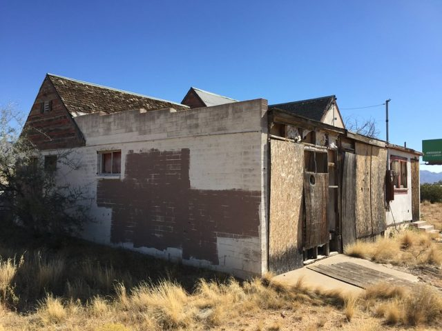 Boarded up cement building