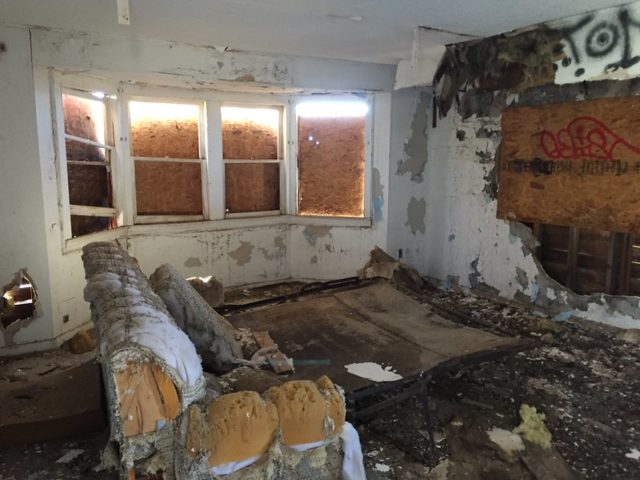 Rotting couch inside a dilapidated room