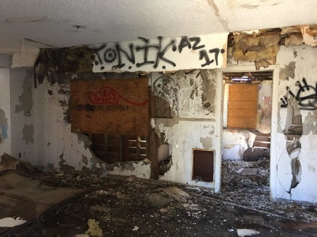 Rotting interior of a building with graffiti on the walls