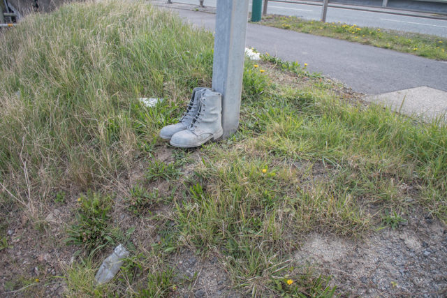 Boots lined up against a wooden post