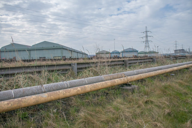 Metal pipelines with buildings in the background