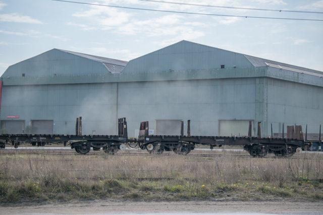 Railway cars in front of steel buildings