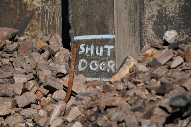 """""""Shut Door"""" painted on crumbled concrete at the Dorman Long tower site"""