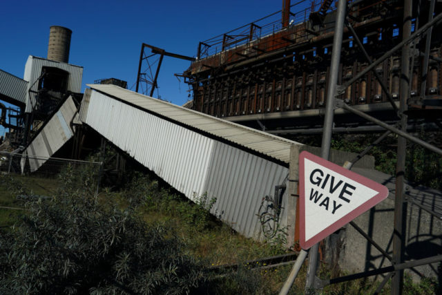 """""""Give Way"""" sign beside a metal shute that's been cut in half"""
