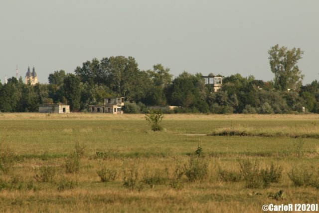 Buildings covered by trees in the horizon at Kalocsa Airfield