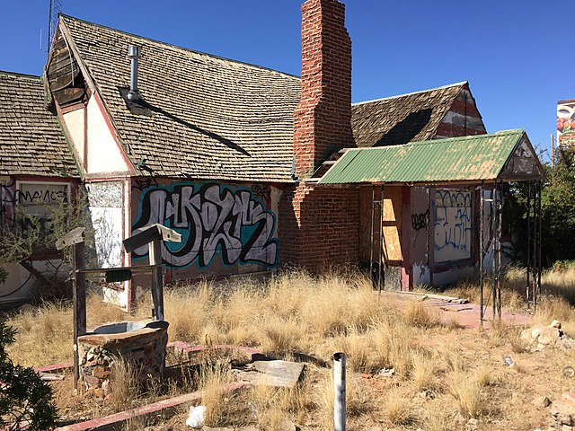 Dilapidated building with a wishing well in the front yard