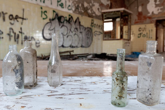 Empty glass bottles atop a table