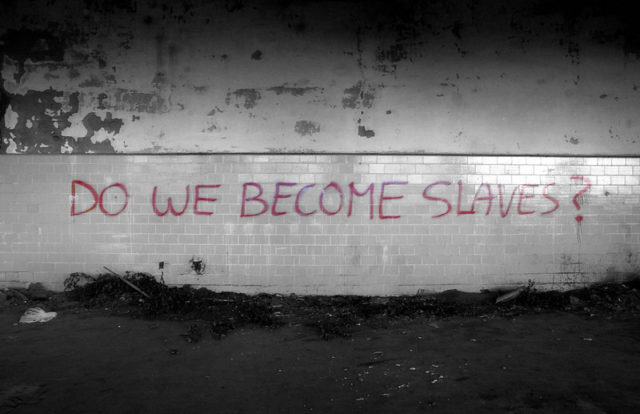 """""""DO WE BECOME SLAVES?"""" graffiti on a wall"""