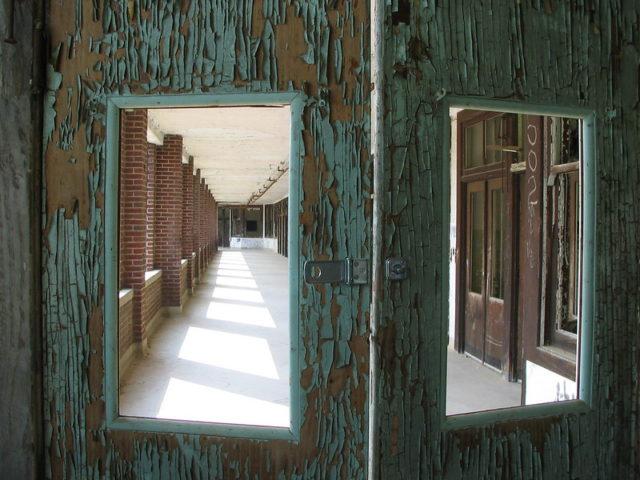 Looking into a hallway via windows in two doors