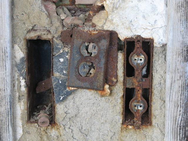 Rusty electrical plugs in the wall