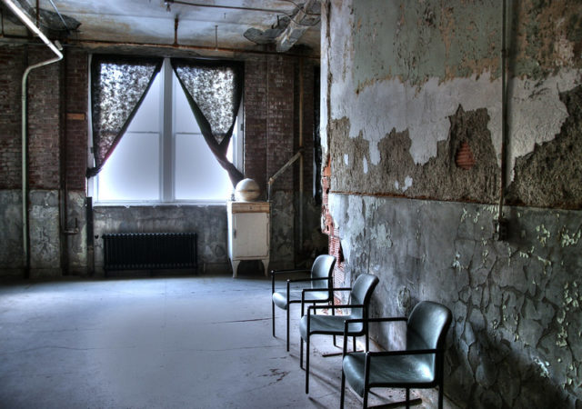 Chairs against the wall of a room lit by a large window
